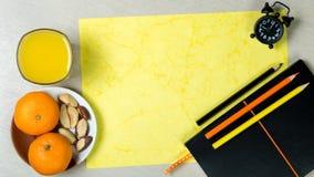 Accessoires de bureau avec le verre de jus d'orange et sain lumineux Image stock