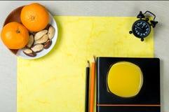Accessoires de bureau avec le verre de jus d'orange et sain lumineux Image libre de droits