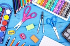 Accessoires de bureau et d'école sur les conseils bleus, de nouveau au concept d'école Photos libres de droits
