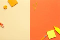 Accessoires de bureau sur le fond jaune et orange Image libre de droits