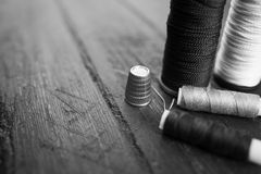 Accessoires de couture : bobines de fil, aiguille, dé sur la table en bois Pékin, photo noire et blanche de la Chine Mise sur pie Image stock