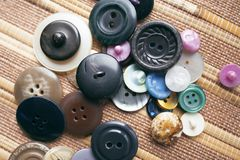 Accessoires de couture - boutons multicolores sur un fond brun Photo stock