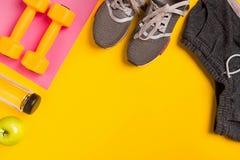 Accessoires de forme physique sur le fond jaune Espadrilles, bouteille de l'eau et haltères Photographie stock