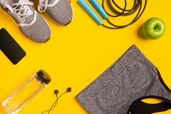 Accessoires de forme physique sur le fond jaune Les espadrilles, la bouteille de l'eau, les écouteurs et le sport complètent Photo stock