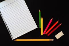 Accessoires de fournitures de bureau d'école ou sur le fond en bois foncé Crayon, gomme, agrafe colorée et page rayée de carnet Photographie stock
