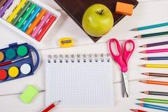 Accessoires de livre et d'école sur les conseils blancs, de nouveau au concept d'école Photos stock