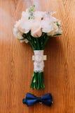 Accessoires de mariage : noeud papillon du marié, bouquet nuptiale de roses blanches sur la table en bois Photos stock