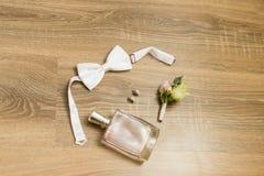 Accessoires de mariage Parfum rose, boucles d'oreille nuptiales avec des diamants, bowtie blanc et boutonniere avec de petites ro Image stock