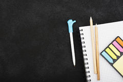 Accessoires de papeterie : un carnet pour des notes, autocollants colorés, crayons, un stylo avec un chapeau avec le symbole de l Images libres de droits