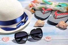 Accessoires de plage lunettes de soleil et un chapeau d'été avec le Vietnamien et les coquillages sur un fond en bois bleu photo libre de droits