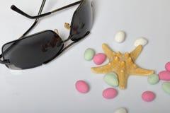 Accessoires de vacances d'été sunglasses Cailloux et étoiles de mer colorés sur un fond blanc image libre de droits