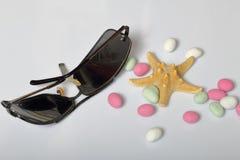 Accessoires de vacances d'été sunglasses Cailloux et étoiles de mer colorés sur un fond blanc photographie stock
