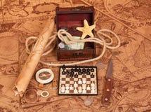 Accessoires de voyage : rouleau, boussole, échecs, trésor des cartes antiques Photographie stock libre de droits