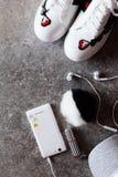 Accessoires du ` s de fille - smartphone blanc, écouteurs, espadrilles et chapeau gris Image stock