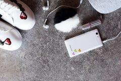 Accessoires du ` s de fille - smartphone blanc, écouteurs, espadrilles et chapeau gris Photographie stock libre de droits