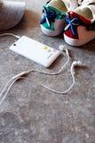 Accessoires du ` s de fille - smartphone blanc, écouteurs, espadrilles et chapeau gris Image libre de droits