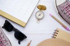 Accessoires et boussole de voyageur sur le fond en bois blanc luttez Photos stock