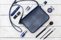 Accessoires féminins Sac à main bleu-foncé et maquillage bleu La plate Photographie stock libre de droits