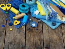Accessoires jaunes et bleus pour la couture sur le fond en bois brun Tricotage, broderie, cousant Petite entreprise Revenu de h Images stock