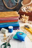 Accessoires pour piquer et une pile de tissus colorés pour piquer sur le fond de la boîte avec des coquillages images stock