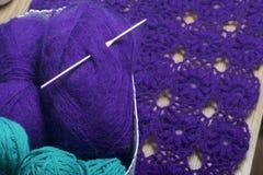 Accessoires pour tricoter et faire du crochet Souffles des fils de couleur violette et verte Contre le contexte d'un produit tric Photos libres de droits