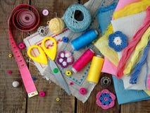Accessoires roses, jaunes et bleus pour la couture sur le fond en bois Tricotage, broderie, cousant Petite entreprise Revenu de h Photo libre de droits