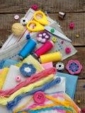 Accessoires roses, jaunes et bleus pour la couture sur le fond en bois Tricotage, broderie, cousant Petite entreprise Revenu de h Photographie stock libre de droits