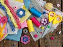 Accessoires roses, jaunes et bleus pour la couture sur le fond en bois Tricotage, broderie, cousant Petite entreprise Revenu de h Photos stock