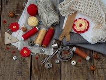 Accessoires rouges et gris pour la couture sur le fond en bois Tricotage, broderie, cousant Petite entreprise Revenu de passe-tem Image stock