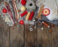 Accessoires rouges et gris pour la couture sur le fond en bois Tricotage, broderie, cousant Petite entreprise Revenu de passe-tem Photos stock
