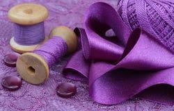 Accessoires violets pour la couture : tissu, ruban, boutons, bobine Photographie stock libre de droits