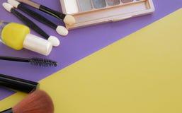 Accessori cosmetici La spazzola per arrossisce, spazzola, vernicia su un fondo giallo e porpora fotografia stock