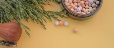 Accessori cosmetici Spazzoli, arrossisca, rossetto, il ramo verde su un giallo, fondo crema immagine stock