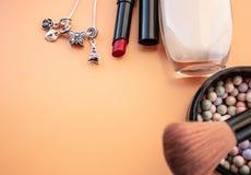 Accessori cosmetici Spazzoli, arrossisca, rossetto, la crema su un giallo, fondo crema Con spazio vuoto a sinistra immagine stock