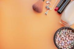 Accessori cosmetici Spazzoli, arrossisca, rossetto, la crema su un giallo, fondo crema Con spazio vuoto a sinistra fotografia stock