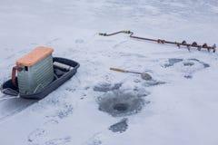 Accessori del primo piano per l'inverno che pesca bugia sul fiume congelato con il foro fotografie stock libere da diritti
