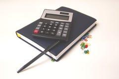 Accessori dell'ufficio con il calcolatore ed il blocco note sullo scrittorio immagine stock
