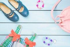 Accessori della bambina Borsa rosa con il vestito variopinto, il cerchietto, i legami dei capelli e le scarpe su fondo di legno p immagine stock