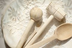 Accessori della cucina Cucchiaio di legno, bastone e un pestello della carne su un piatto decorato ceramico immagini stock