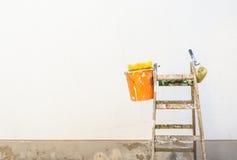 Accessori della pittura su una scala davanti ad una parete esteriore vuota della casa Fotografia Stock Libera da Diritti