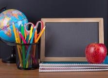 Accessori della scuola con la lavagna in bianco Fotografia Stock