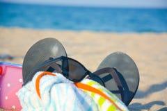 Accessori della spiaggia come occhiali da sole, pantofole, asciugamano, giocattoli sulla sabbia Fotografia Stock Libera da Diritti