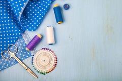 Accessori di cucito su un fondo di legno blu fotografie stock