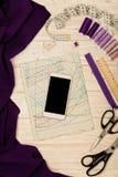 Accessori di cucito, tessuto, modelli e un telefono cellulare di bianco Fotografie Stock Libere da Diritti