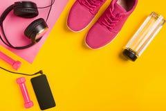 Accessori di forma fisica su fondo giallo Scarpe da tennis, bottiglia di acqua, cuffie ed astuto fotografia stock libera da diritti