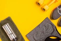 Accessori di forma fisica su un fondo giallo Le scarpe da tennis, la bottiglia dell'acqua, astuti, asciugamano e sport completano immagini stock libere da diritti