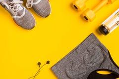Accessori di forma fisica su un fondo giallo Le scarpe da tennis, la bottiglia dell'acqua, le cuffie e lo sport completano immagini stock libere da diritti