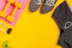 Accessori di forma fisica su un fondo giallo Scarpe da tennis, bottiglia di acqua, mela e teste di legno immagine stock