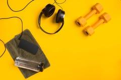 Accessori di forma fisica su un fondo giallo Teste di legno, bottiglia di acqua, asciugamano e cuffie immagini stock libere da diritti