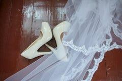 Accessori di nozze Scarpe e velo nuziali sul pavimento di legno alla preparazione di mattina di nozze fotografia stock